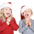 Two children wearing Santa hats eating candy canes — Stock Photo