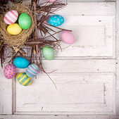 Easter eggs in nest on antique panel — Stock Photo