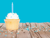 Single cupcake with blue candle and sprinkles — Stock Photo