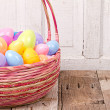 Plastic easter eggs in easter basket — Stock Photo