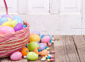 Plastic easter eggs and candy — Stock Photo