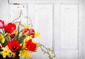 Spring flowers with a wooden background — Stock Photo