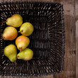 Pears in a black basket — Stock Photo