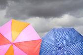 Umbrellas on cloudy background — Stock Photo
