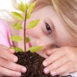 Child with plant smiling — Stock Photo