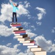 Child on staircase of books — Stockfoto