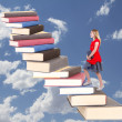 Royalty-Free Stock Photo: Teen climbing a staircase of books