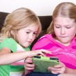 Children or sisters using tablet — Stock Photo