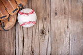 Baseball and mitt on wooden background — Stock Photo
