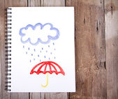 Painting of cloud and rain with umbrella on notebook — Stock Photo
