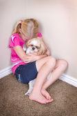 Sad child and dog sitting in corner — Stock Photo