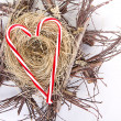 Candy canes in the shape of a heart on a nest — Stock Photo