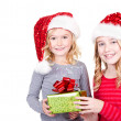 Sisters or two young girls wearing Santa hats — Stock Photo
