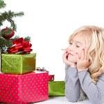 Child next to a Christmas tree — Stock Photo
