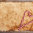 Torn paper onwooden background with candy canes — Stock Photo