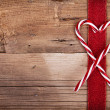 Candy canes and ribbon on wooden background — Stock Photo