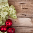 Christmas ribbon and ornaments on a wooden background — Stock Photo #35674583