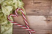 Christmas ribbon and candy canes on wooden background — Zdjęcie stockowe