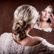 Woman looking into a broken mirror — Stock Photo