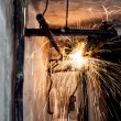 Professional welder cutting metallic pipes and grinding steel — Stock Photo
