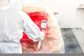 Automotive industry - car painter painting a red car — Stock Photo