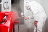 Automotive industry - worker painting and working — Stock Photo