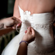 Maid of honor helping the bride to put her wedding dress — Stock Photo