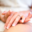 Bride's hands with expensive engagement ring on wedding dress — Stock Photo