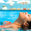 Young woman enjoying water and sun in outdoor swimming pool — Stock Photo