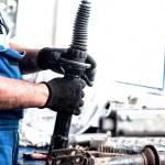 Auto engineer mechanic working on car shock absorber — Stock Photo