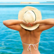 Happy woman enjoying the sun on seaside beach with hat in summer — Stock Photo