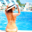 Hot beautiful woman in hat and bikini standing and relaxing at the pool — Stock Photo