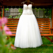 White wedding dress hanging on a shoulders in garden — Stock Photo