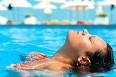 Jeune femme appréciant l'eau et soleil dans la piscine extérieure — Photo