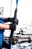 Auto engineer mechanic working on car shock absorber — Stock Photo