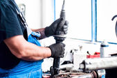 Auto car mechanic working on car shock absorber and parts of car — Stock Photo