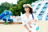 Beautiful woman going sunbathing at ocean resort on local beach — Stock Photo