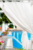 Close-up detail of white sunbeds inside tend by a modern pool — Stock Photo
