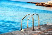 Piscina com vista para o oceano e escadas — Fotografia Stock