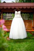Biała suknia wisi na barkach w ogrodzie — Zdjęcie stockowe