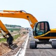 Heavy duty excavator working in sand on the side of road construction site — Stock Photo
