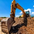 Yellow excavator moving soil and sand on road construction site — Foto de stock #32150853