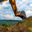 Loader Excavator standing in sandpit with risen bucket over cloudy sky — Stock Photo