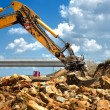 Worker moving rocks with excavator on construction site — Stock Photo
