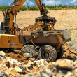 Excavator loading heavy duty dumper truck with rocks — Stock Photo