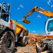Big, industrial excavator on new construction site loading dumper trucks — Stock Photo