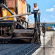 Pavement machine laying fresh asphalt or bitumen on top of the gravel base — Stock Photo
