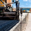 Stock Photo: Industrial pavement truck or machine laying fresh bitumen and asphalt