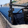 Stock Photo: Industrial pavement truck laying fresh asphalt on construction site
