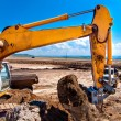 Industrial excavator bulldozer digging in sandpit and loading soil — Stock Photo